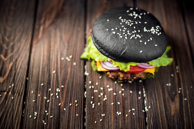 Zelfgemaakte zwarte hamburger met kaas. cheeseburger met zwart broodje o