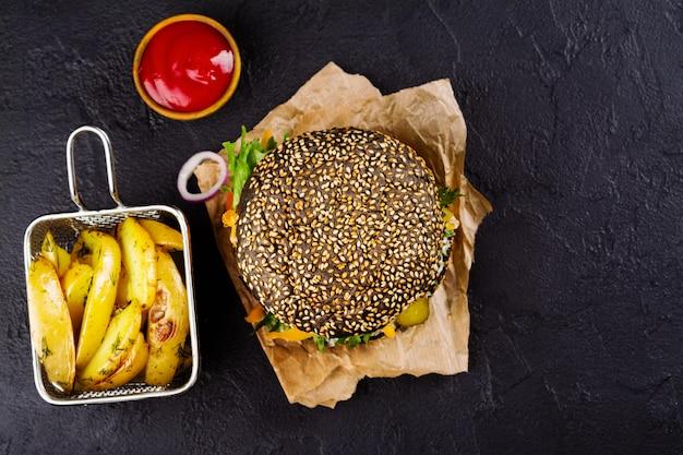Zelfgemaakte zwarte hamburger met tzatziki saus, geraspte kaas en vlees stopverf.