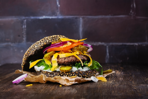 Zelfgemaakte zwarte hamburger met tzatziki saus, geraspte kaas en vlees stopverf