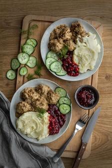 Zelfgemaakte zweedse gehaktballetjes met aardappelpuree, cranberrysaus en komkommer