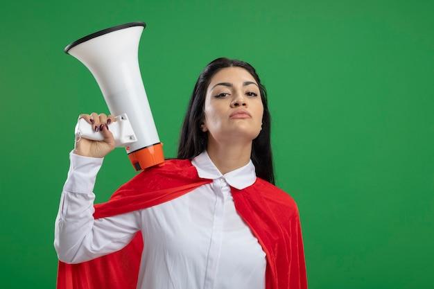 Zelfgenoegzaam jong kaukasisch superheldmeisje dat luide spreker bij de hand houdt en zelfverzekerde gezichtsuitdrukkingen toont die op groene muur met exemplaarruimte worden geïsoleerd
