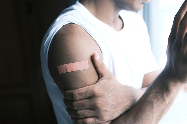 Zelfklevend verband op de arm van de jonge man
