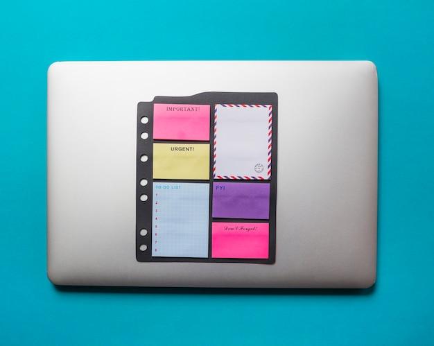 Zelfklevende nota's met envelop die op laptop tegen blauwe achtergrond worden geplakt