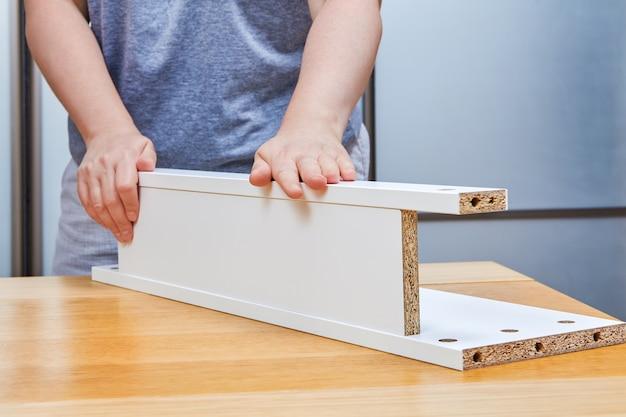 Zelfmontage van meubels thuis, vrouwenhanden voegen onderdelen samen.