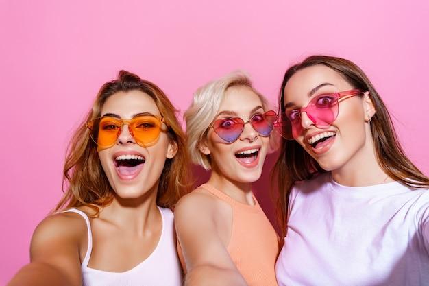 Zelfportret van drie grappige funky emotionele expressieve mooie meisjes gebaar poseren op roze achtergrond...