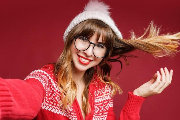 Zelfportret van gelukkig langharige vrouw in winterkleren