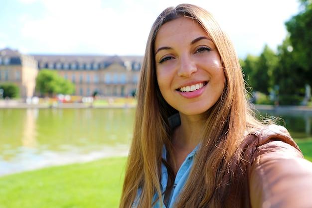 Zelfportret van glimlachende jonge vrouw voor neues schloss van stuttgart, duitsland