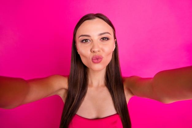 Zelfportret van haar ze mooi aantrekkelijk mooi innemend lief vrolijk vrolijk lief langharig meisje je kus sturen geïsoleerd op heldere levendige glans levendige roze fuchsia kleur achtergrond