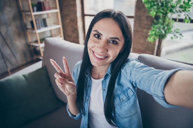 Zelfportret van haar ze mooi aantrekkelijk mooi mooi schattig vrolijk vrolijk brunette meisje toont vsign vrije tijd besteden vrije tijd thuis blijven in moderne loft baksteen industrieel huis appartement