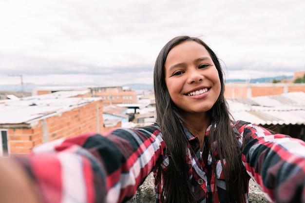Zelfportret van mooi meisje in sloppenwijk. slecht zuigelingenconcept