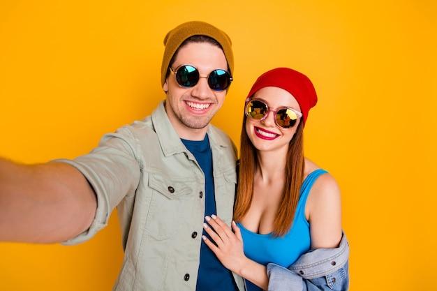 Zelfportret van mooie aantrekkelijke vrolijke vrolijke paar vakantie vakantie reis weekend omarmen geïsoleerd over heldere levendige glans levendige gele kleur achtergrond