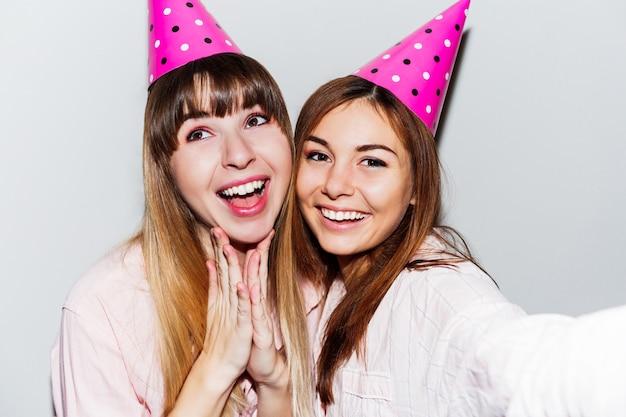 Zelfportret van twee glimlachende vrouwen in roze papieren verjaardagshoeden. vrienden die roze pyjama's dragen.