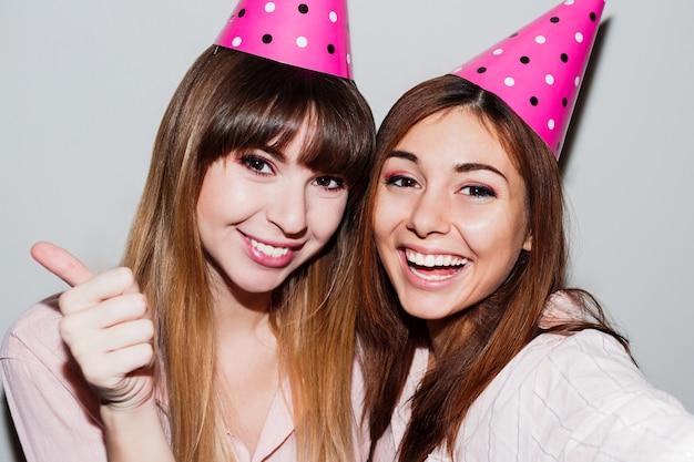 Zelfportret van twee vrouwen in roze papieren verjaardagshoedjes. vrienden die roze pyjama's dragen