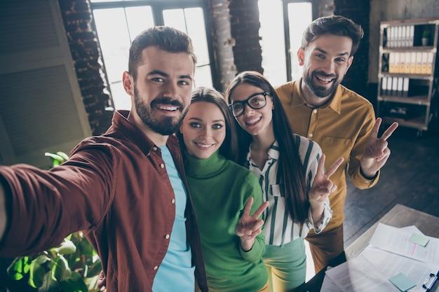 Zelfportret van vier mooie aantrekkelijke vriendelijke blije vrolijke vrolijke professionele mensenpartners met v-sign met leuke dag