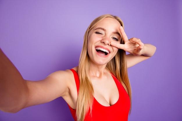 Zelfportret van vrolijke blonde met v-teken