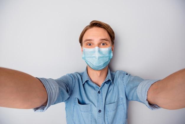 Zelfportret van zijn aardige, aantrekkelijke blonde man met veiligheidsgaasmasker mers cov griepbesmetting geval preventie houd sociale afstand geïsoleerd over grijze kleur achtergrond