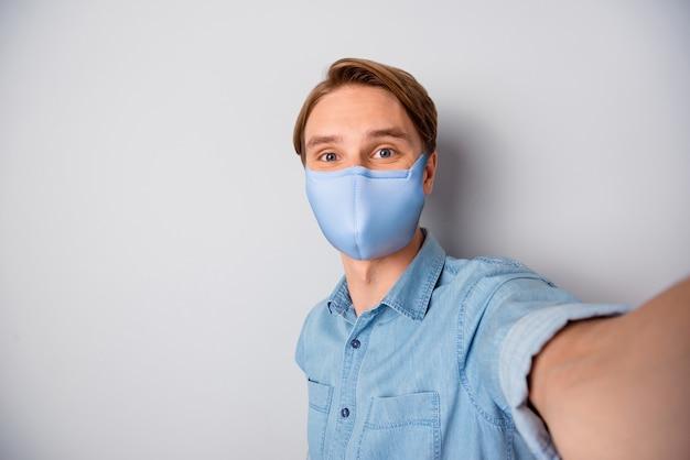 Zelfportret van zijn aardige gezonde aantrekkelijke man met textiel trendy herbruikbare veiligheid blauw masker stop griep wuhan china ziekte gezondheidszorg immuniteit geïsoleerd over grijze kleur achtergrond