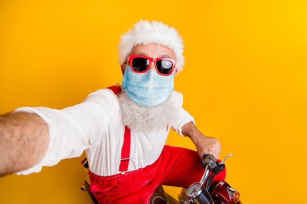 Zelfportret van zijn aardige grappige funky oudere man die een kerstmankostuum draagt met een veiligheidsgaasmasker dat op een bromfiets rijdt en geschenken levert blijf thuis geïsoleerd helder levendig glans levendige gele kleur achtergrond