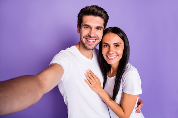 Zelfportret van zijn hij haar ze mooi aantrekkelijk charmant lief lief vrolijk vrolijk blij paar tijd doorbrengen vakantie vakantie knuffelen geïsoleerd op paars violet lila kleur pastel achtergrond