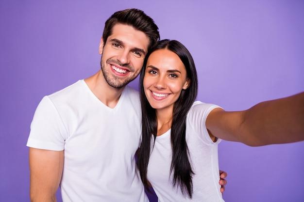 Zelfportret van zijn hij haar ze mooi aantrekkelijk charmant lief schattig vrolijk vrolijk paar soulmate tijd doorbrengen knuffelen geïsoleerd op paars violet lila kleur pastel achtergrond