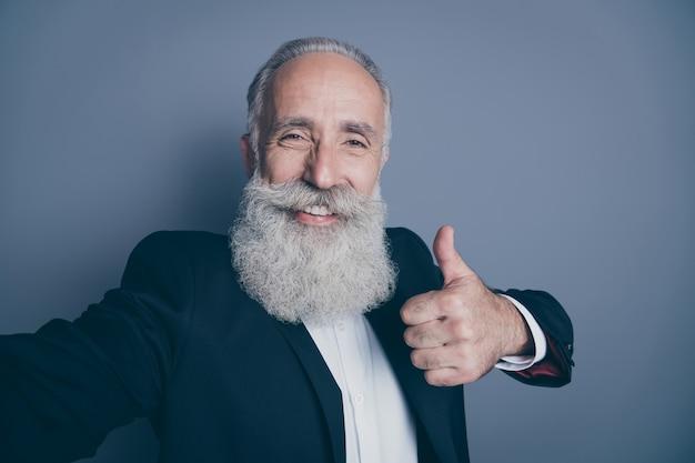 Zelfportret van zijn hij mooie aantrekkelijke trendy inhoud vrolijke vrolijke grijsharige man toont thumbup nieuwe nieuwigheid oplossing advertentie geïsoleerd over donkergrijze pastelkleur achtergrond