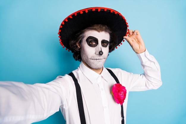 Zelfportret van zijn knappe griezelige, griezelige man heer die het aanraken van sombrero santa muerte catrina thema feestelijk evenement viering geïsoleerd helder levendig glans levendige blauwe kleur achtergrond draagt