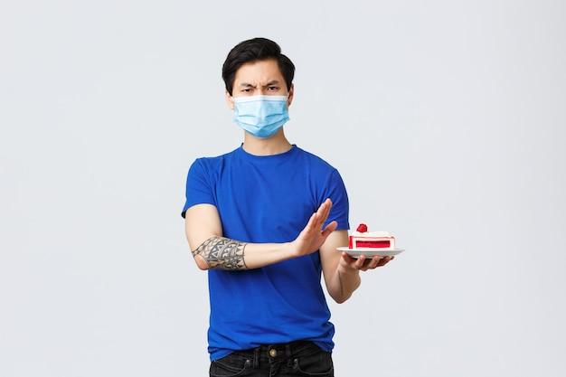Zelfquarantaine, thuislevensstijl en feestconcept. aziatische teleurgestelde man die verjaardag viert, stuktaart verwerpt die niet in de stemming is, boos is terwijl hij op een grijze achtergrond van een medisch masker staat.