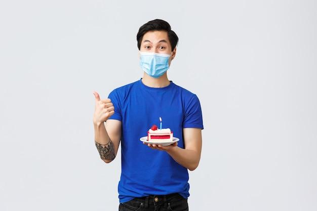 Zelfquarantaine, thuislevensstijl en feestconcept. blije tevreden aziatische man bestelde thuisbezorging van verjaardagstaart, duim omhoog terwijl hij hem vasthield, draag medisch masker, blij met afhaalmaaltijden