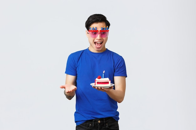 Zelfquarantaine, thuislevensstijl en feestconcept. opgewonden vrolijke aziatische man die verjaardag viert in glazen, kijkend naar heerlijke afhaalmaaltijden bestelde verjaardagstaart met brandende kaars, wens doen