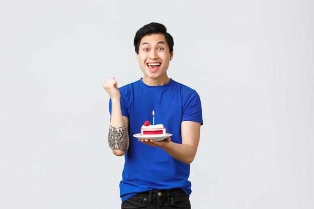Zelfquarantaine, thuislevensstijl en feestconcept. verheugende gelukkige aziatische man die verjaardag viert, vuistpomp en glimlacht die wens doet, fluitje van een cent, grijze achtergrond