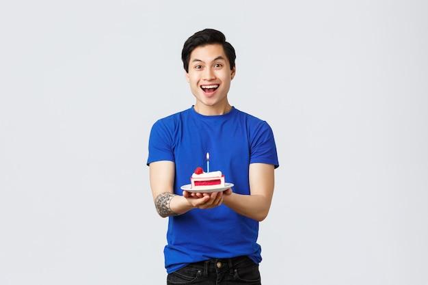 Zelfquarantaine, thuislevensstijl en feestconcept. vrolijke aziatische man die verjaardag viert, stuktaart vasthoudt en vrolijk glimlacht, wens doet, droomt van iets, grijze achtergrond.