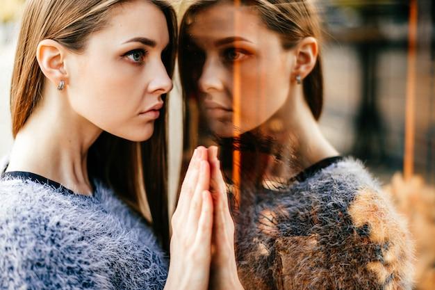 Zelfreflectieportret van verbazend jong meisje in weerspiegeld venster