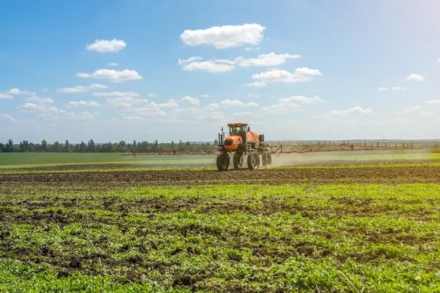 Zelfrijdende veldspuit werkt op een veld onder een blauwe lucht met wolken