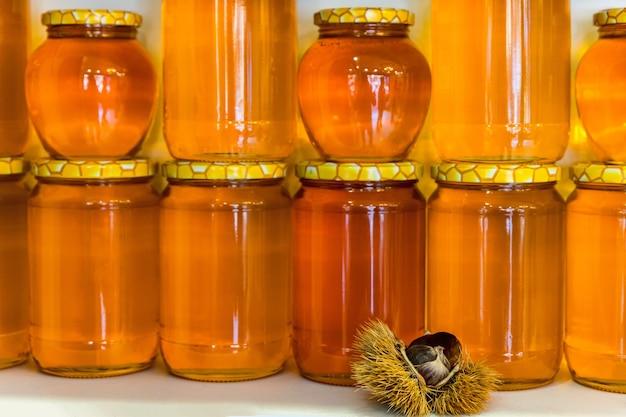 Zelfs rijen blikken met kastanjeshoning met gele deksels in een doorzichtige glazen pot versierd met rauwe kastanjes. selectieve aandacht