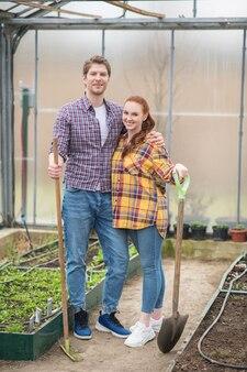 Zelfstandig ondernemerschap. jonge volwassenen knuffelen man en vrouw in vrijetijdskleding met tuingereedschap glimlachend in hun kas