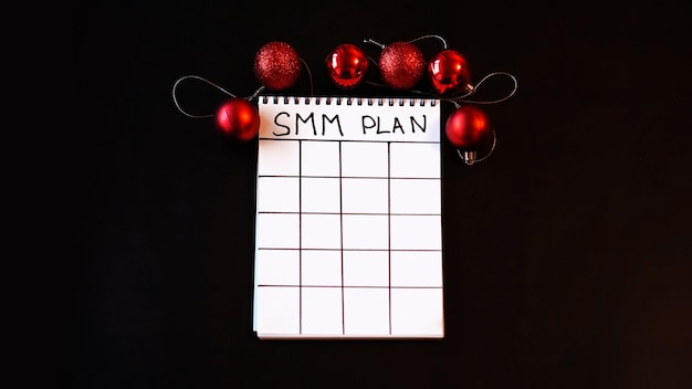 Zelfstandig project. smm-abonnement leeg. wit laken op een zwarte feestelijke achtergrond met rode kerstballen