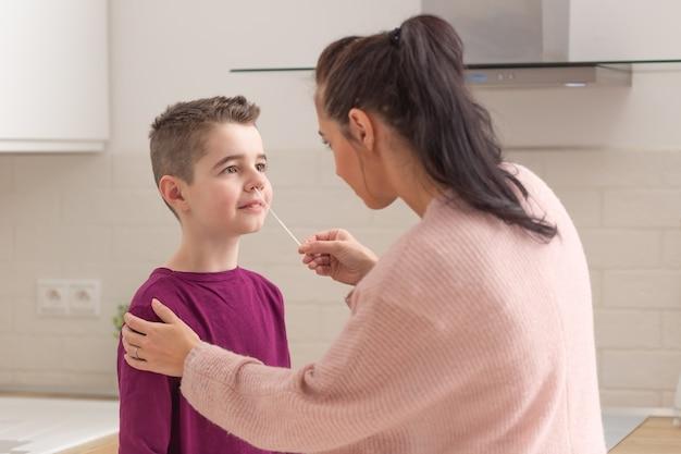 Zelftest voor covid 19 in de keuken terwijl moeder een monster uit de neus van haar zoon neemt met een wattenstaafje.