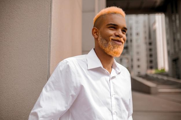Zelfvertrouwen. jonge man met donkere huidskleur in witte kleren ziet er zelfverzekerd uit