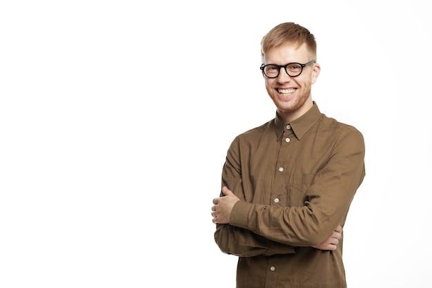 Zelfvertrouwen, vreugde, geluk en succesconcept. portret van knappe positieve jonge man in bruin shirt en bril