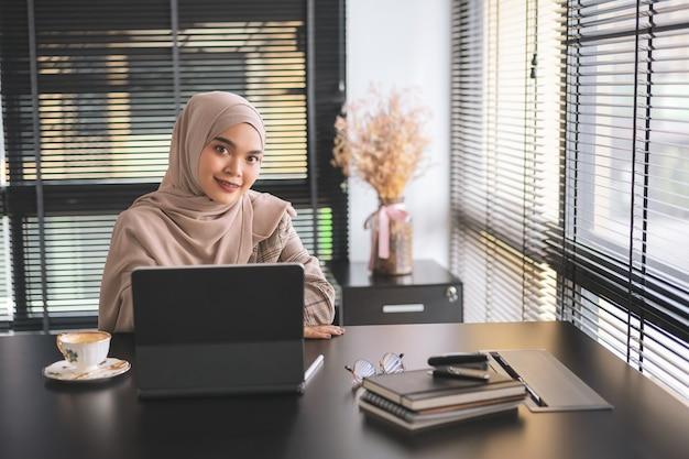 Zelfverzekerd aziatische moslim zakelijke vrouw bruin hijab zitten en werken met laptopcomputer op moderne kantoor.