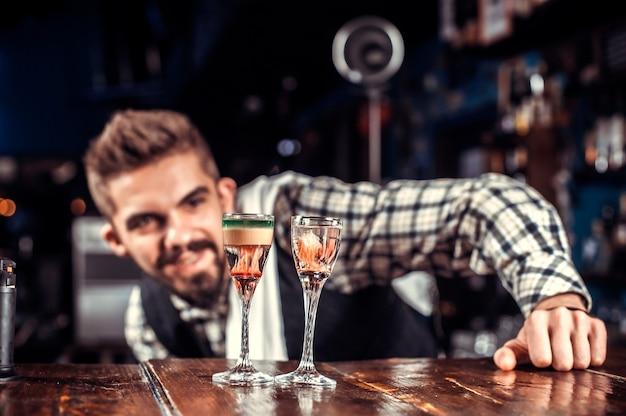 Zelfverzekerd bartending demonstreert zijn professionele vaardigheden terwijl hij naast de bar in de pub staat