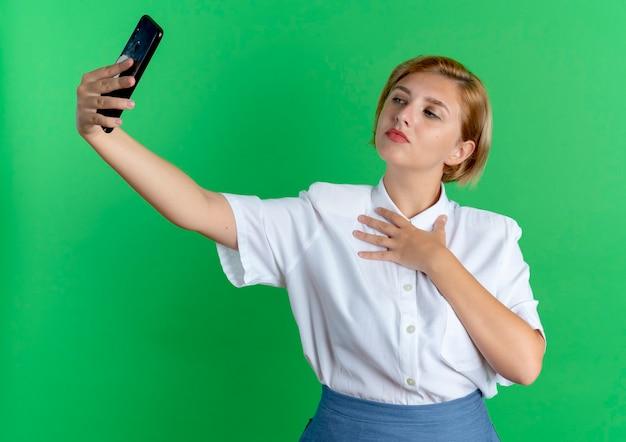 Zelfverzekerd blond russisch meisje kijkt naar telefoon nemen selfie legt hand op borst geïsoleerd op groene achtergrond met kopie ruimte