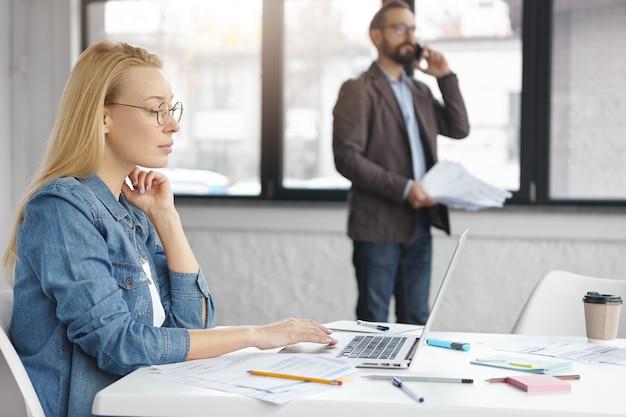 Zelfverzekerd blonde vrouwelijke secretaris gebruikt laptop terwijl baas telefoongesprek heeft