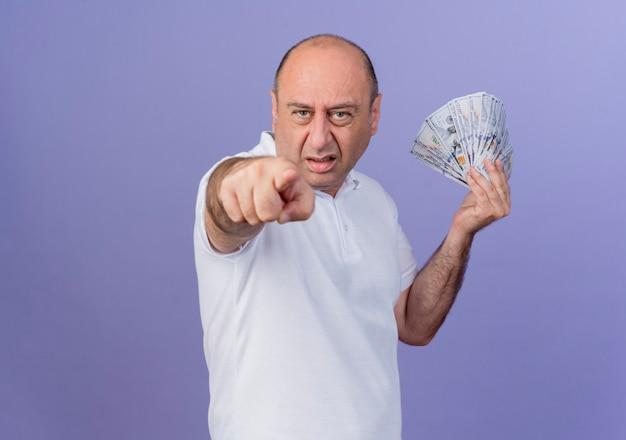 Zelfverzekerd casual volwassen zakenman bedrijf geld en wijzend op camera geïsoleerd op paarse achtergrond met kopie ruimte