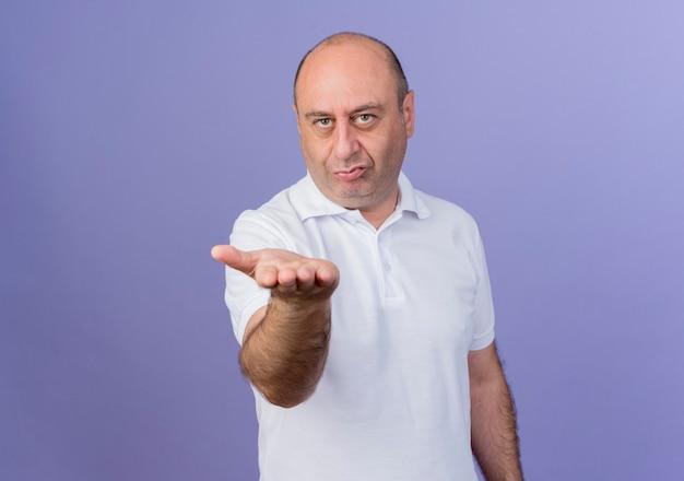 Zelfverzekerd casual volwassen zakenman die zich uitstrekt en lege hand toont op camera geïsoleerd op paarse achtergrond met kopie ruimte