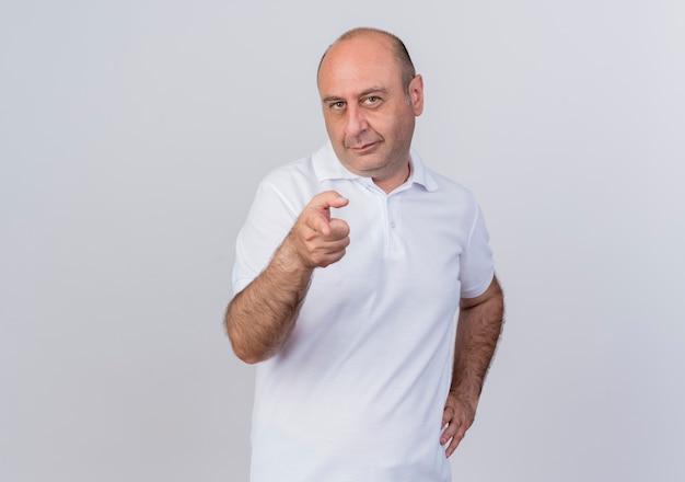Zelfverzekerd casual volwassen zakenman hand zetten taille en wijzend op camera geïsoleerd op een witte achtergrond met kopie ruimte