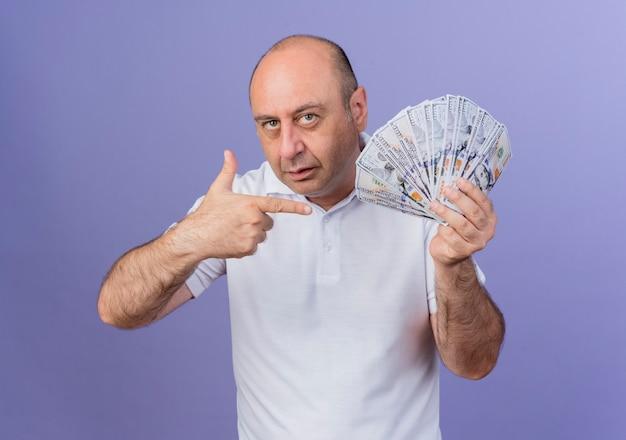 Zelfverzekerd casual volwassen zakenman houden en wijzend op geld geïsoleerd op paarse achtergrond