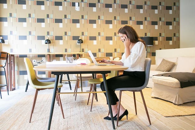 Zelfverzekerd creatieve professional project bespreken met klant op telefoon, zittend aan tafel met laptop en blauwdrukken en typen