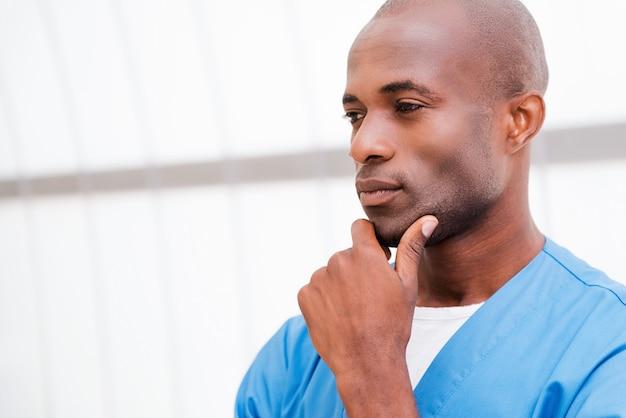 Zelfverzekerd en geconcentreerd. portret van een bedachtzame jonge afrikaanse arts in blauw uniform die de hand op de kin houdt en wegkijkt