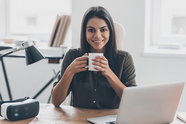 Zelfverzekerd en geïnspireerd. zelfverzekerde jonge vrouw in slimme vrijetijdskleding die een koffiekopje vasthoudt en met een glimlach naar de camera kijkt terwijl ze op haar werkplek op kantoor zit